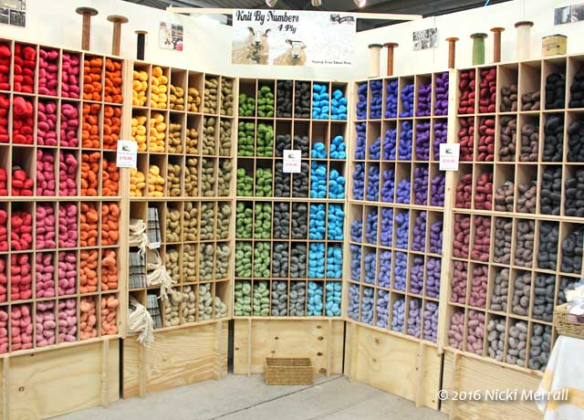 Wooden shelves showing Knit by Numbers yarn arranged by colour and value