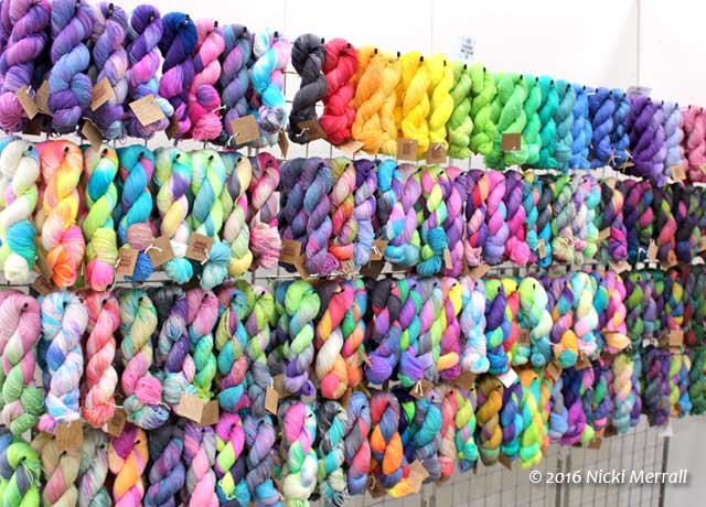 Colourful hanks of hand-dyed yarn on a grid wall