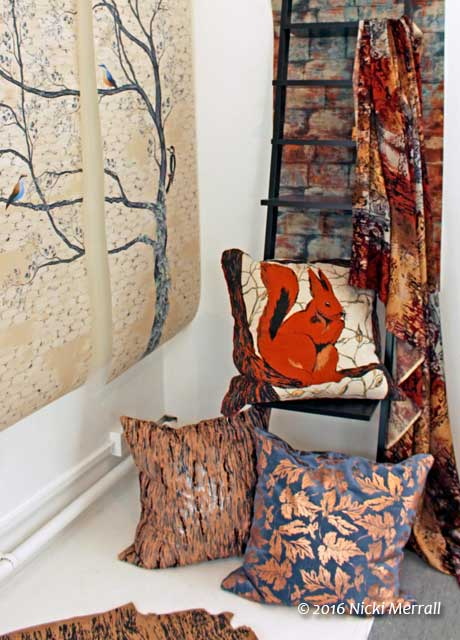 Printed fabrics with a woodland theme used to make cushions and hung on the wall