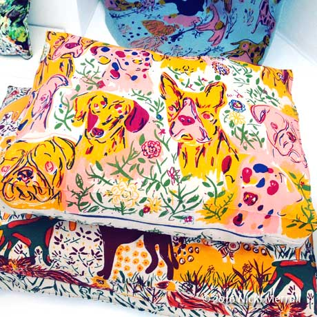 Brightly coloured printed fabrics, with a dog theme, used to cover cushions