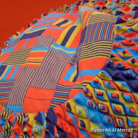 Large patterned knitted cushion with a bright orange, yellow, turquoise and deep blue colour palette