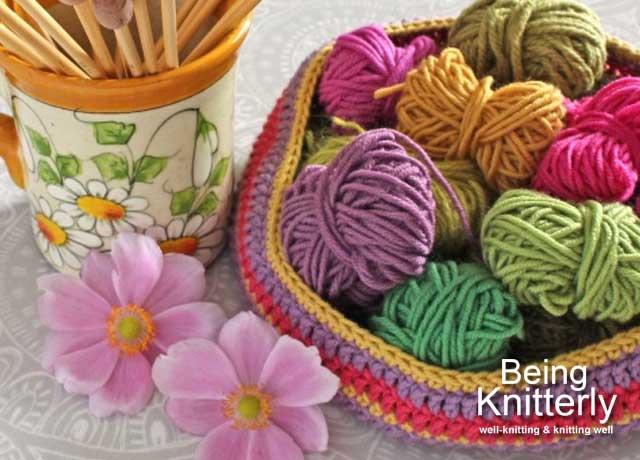 Mug holding bamboo knitting needles and crochet basket full of mini-balls of cotton yarn
