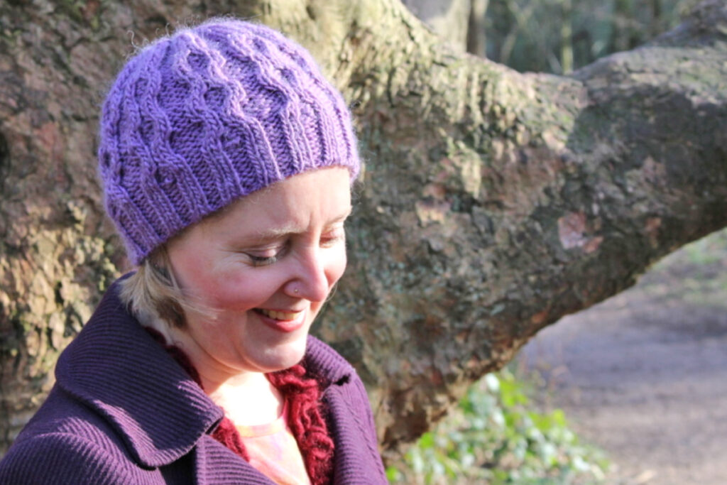 Woman wearing purple cabled beanie
