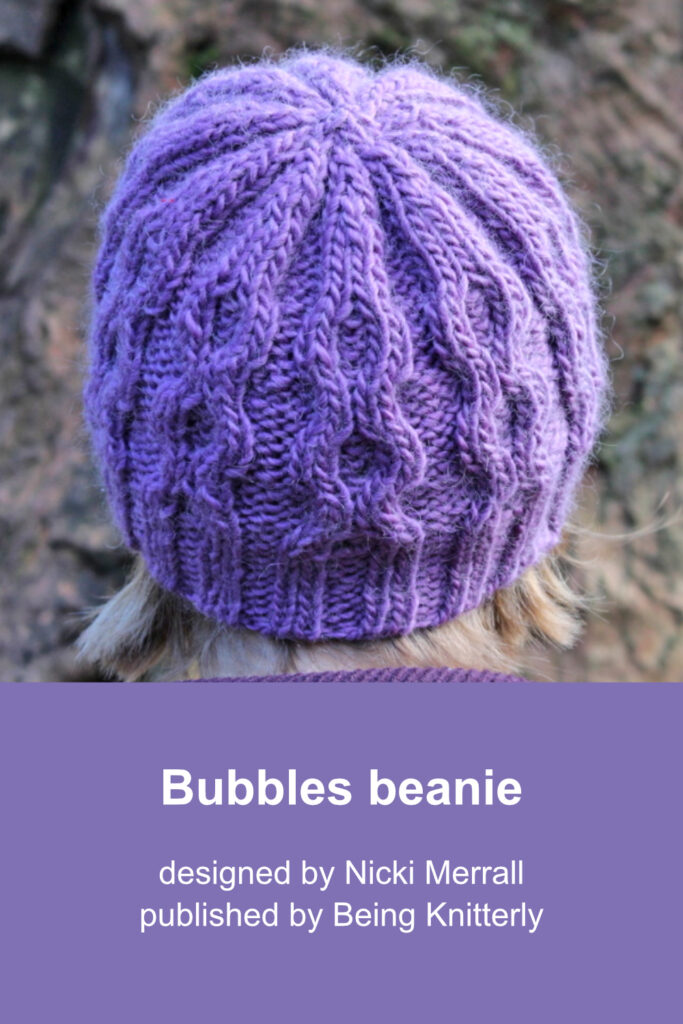 View of purple cabled beanie from back