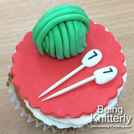 Cup cake covered with red icing, green yarn ball and white knitting needles also make from icing