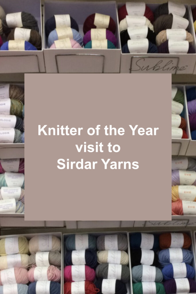 Knitter of the Year visit to Sirdar Yarns in white text on beige square on background showing display of Sirdar yarns