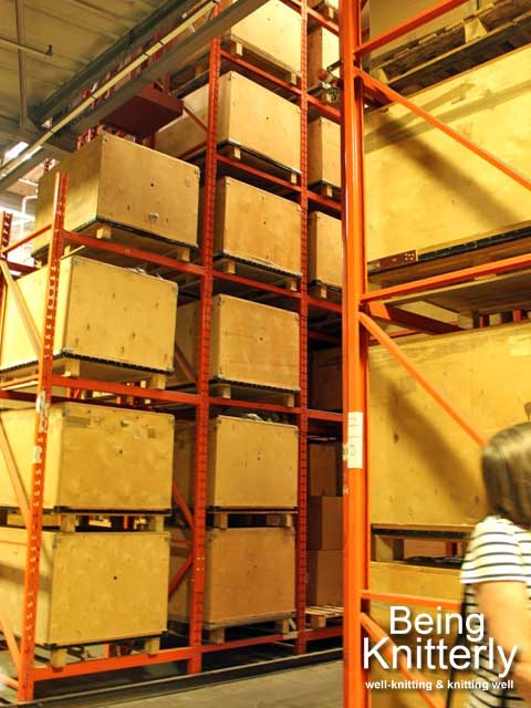 Large boxes containing balls of yarn on shelving in warehouse