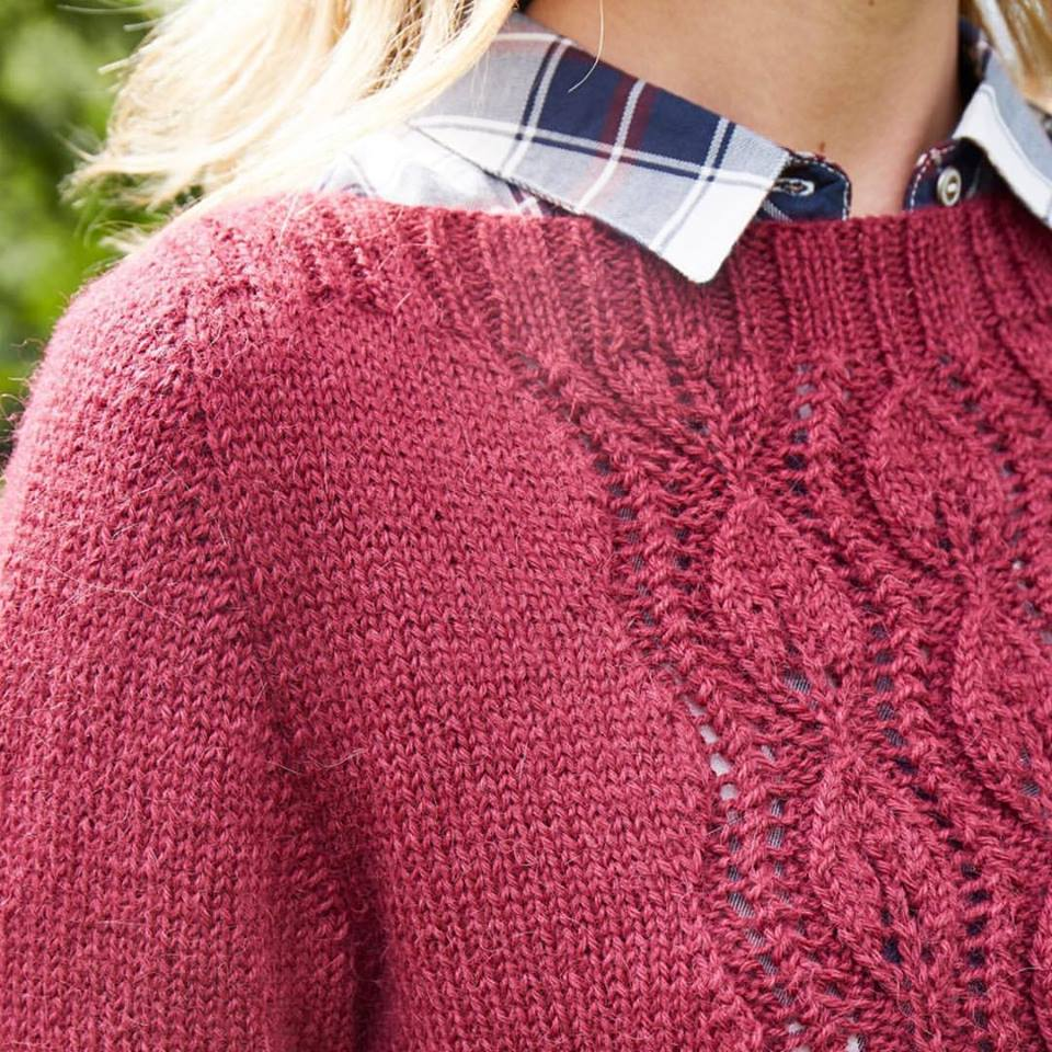 Close-up of front of burgundy fitted hand-knit sweater featuring lace panel with leaf motifs.