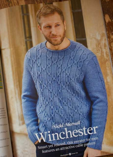Front view of blue wool hand-knit sweater with all-over cable pattern on the front and narrow cable pattern on the sleeve.