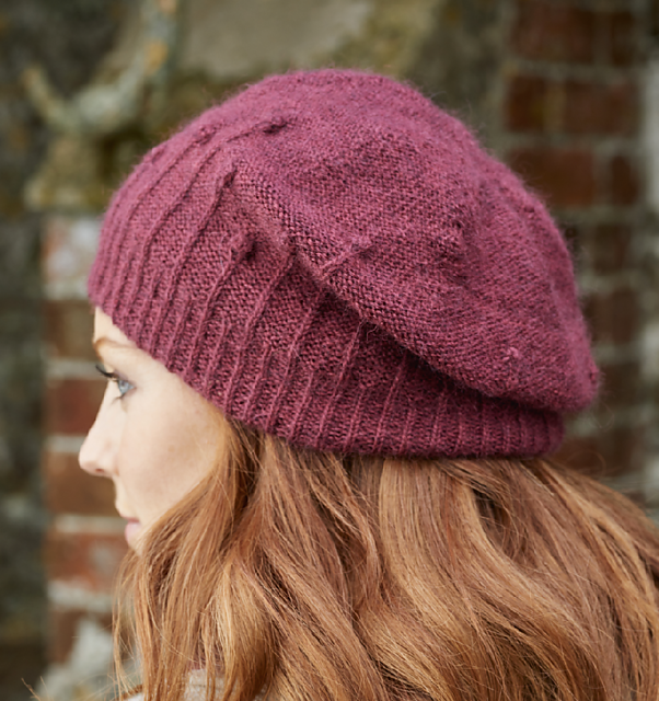 Burgundy wool hand-knit Seed Heads hat features stitch pattern inspired by poppy seed heads