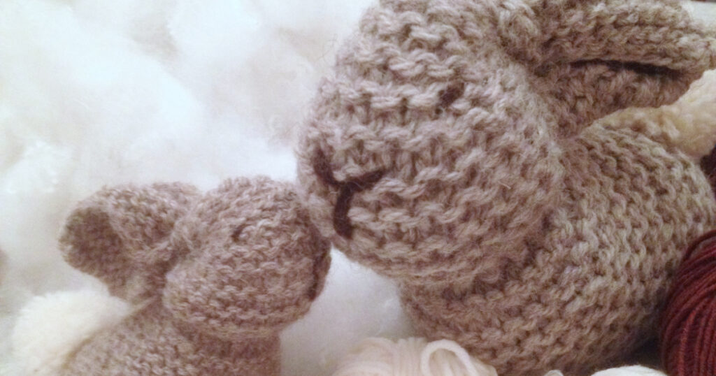 Small and big knitted bunnies made from garter stitch square