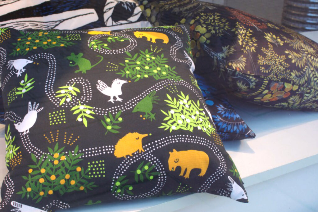 Window display featuring pile of large cushions covered in Finnish fabrics