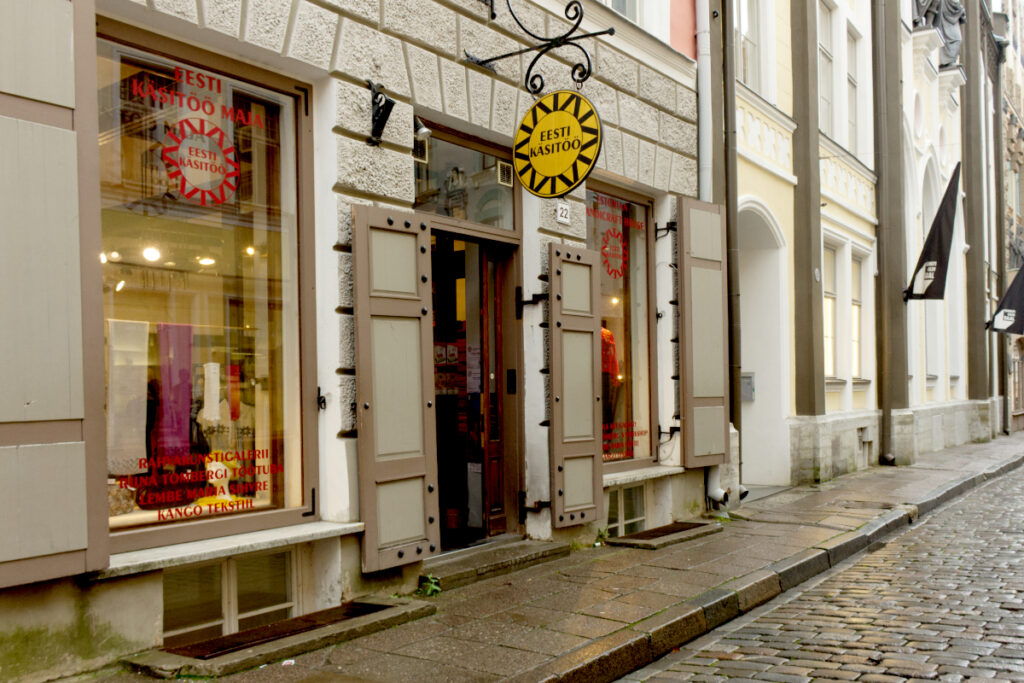 Exterior of an Estonian handicraft centre showing yellow and black circular shop sign above door and small windows with displays of woven and knitted items