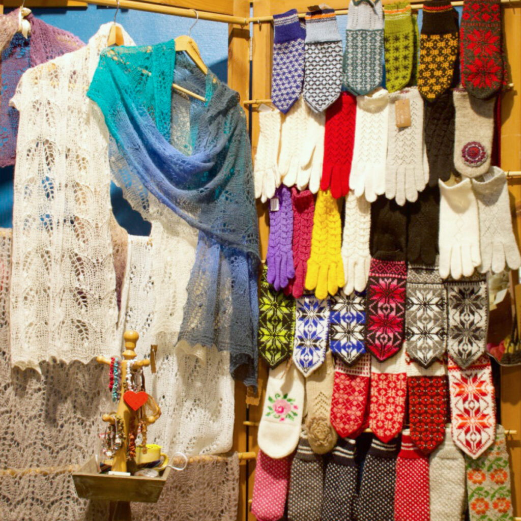 Display of Haapsalu shawls and hand knitted mittens and gloves in lace and colourwork patterns at Jolleri yarn shop