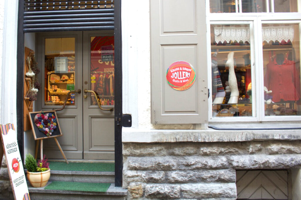 The exterior of Jolleri yarn shop with window display of hand knitted socks and garments