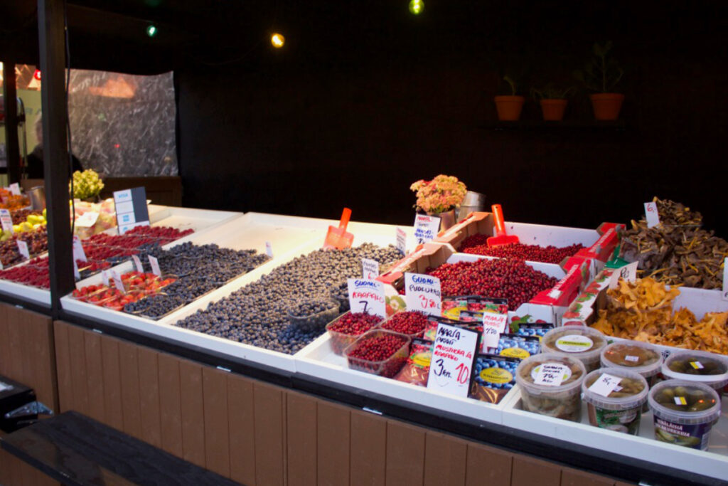 Market stall with display of many different berries and wild mushrooms