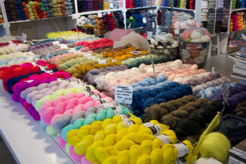 Display of hand-dyed yarn in many colours on table at Snurre yarn shop