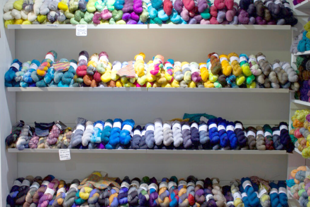 Display of hand-dyed yarn in many colours on shelves at Snurre yarn shop