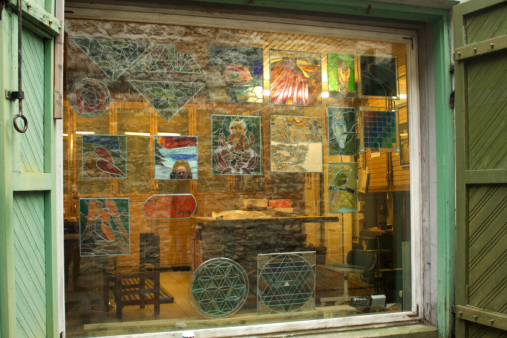 Large window in master craftperson's studio with colourful display of stained glass and wooden shutters either side of the window