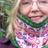 Close-up of woman wearing Fair Isle style cowl with pink and purple large allover motif on white background and green ribs
