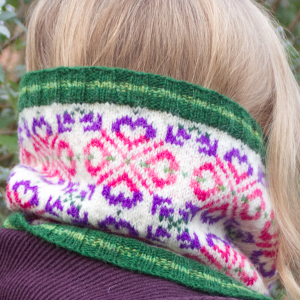 Back view of woman wearing a Fair Isle style cowl with green ribs and large allover motif worked in purple and pinks on white background