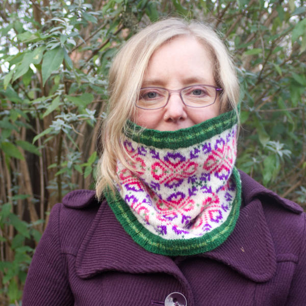 Woman wearing a Fair Isle style cowl with green ribs and large allover motif worked in purple and pinks on white background