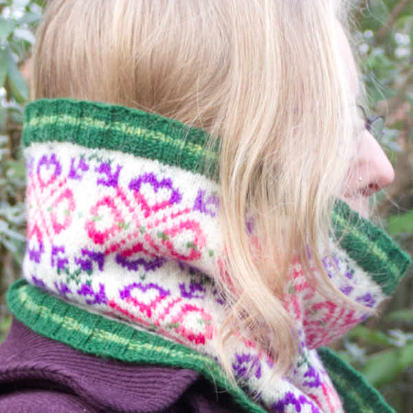 Side view of woman wearing a Fair Isle style cowl with green ribs and large allover motif worked in purple and pinks on white background