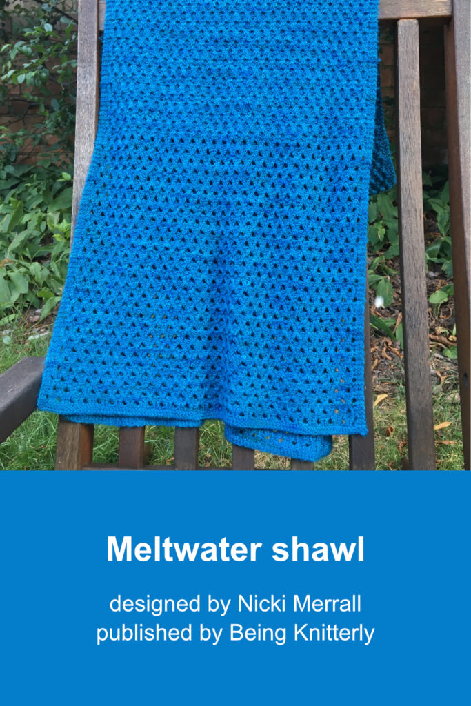Blue-green rectangular shawl, featuring delicate diamond patterns, draped over wooden chair in garden