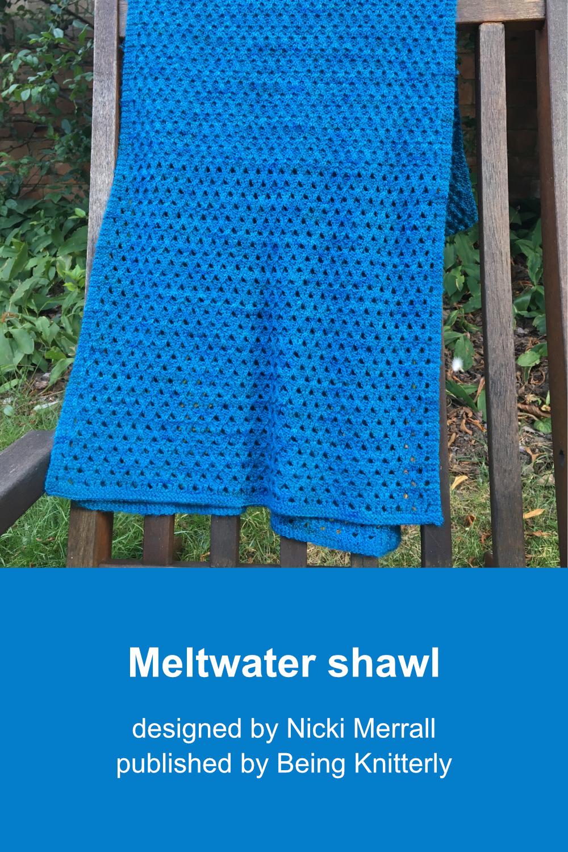 Blue-green rectangular shawl draped over wooden garden chair