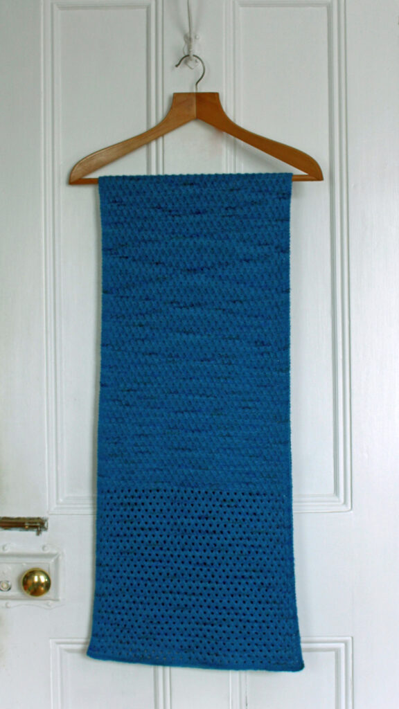 Blue-green rectangular shawl, featuring delicate diamond patterns, hung over wooden coat-hanger on white-painted door