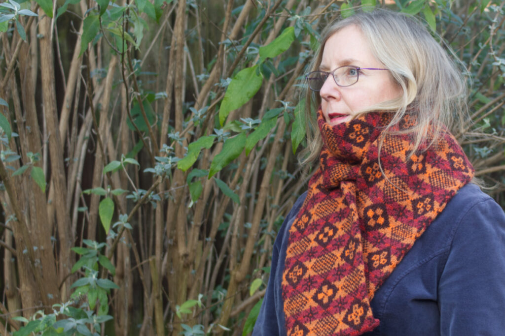 Side view of model wearing hand-knitted Fair Isle style scarf with allover diced pattern featuring six different motifs worked in oranges and red-browns on deep brown background
