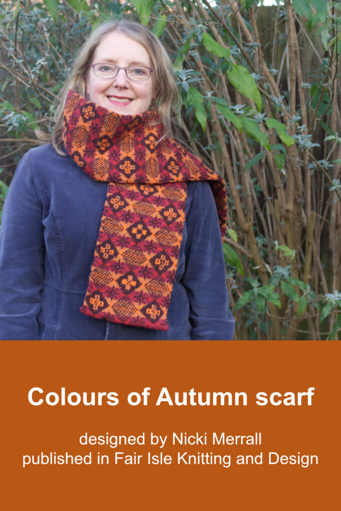 Model wearing hand-knitted Fair Isle style scarf with allover diced pattern featuring six different motifs worked in oranges and red-browns on deep brown background