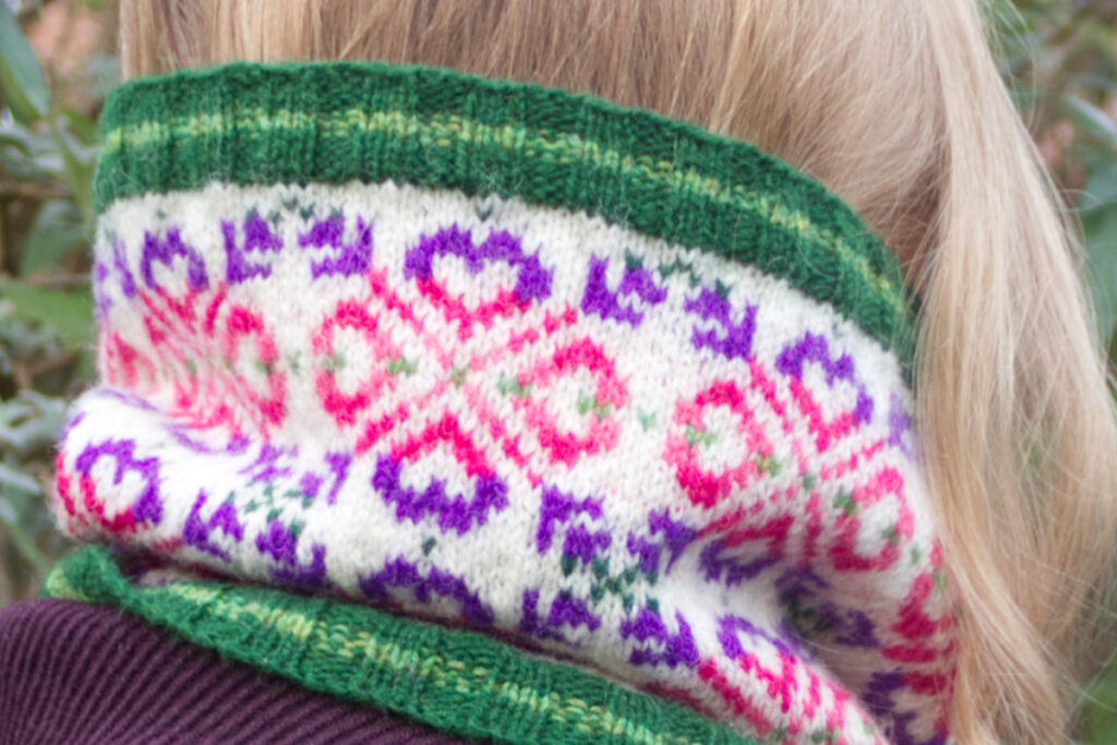 Back view of model wearing hand-knitted Fair Isle style cowl with green ribs and a large all-over motif worked in purple and pinks on a white background