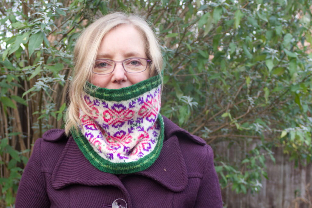 Model wearing hand-knitted Fair Isle style cowl with green ribs and a large all-over motif worked in purple and pinks on a white background