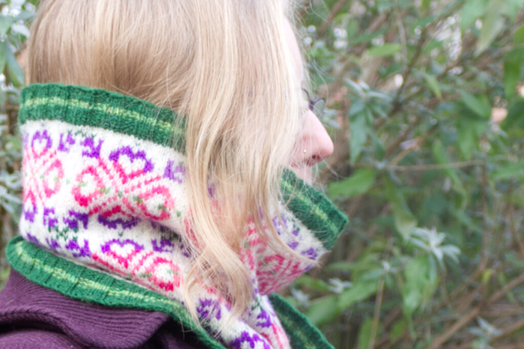 Side view of model wearing hand-knitted Fair Isle style cowl with green ribs and a large all-over motif worked in purple and pinks on a white background