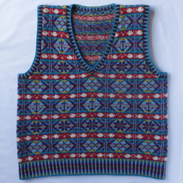 All the Fish sleeveless sweater with fishing inspired motifs in blues, reds white, yellow and purples
