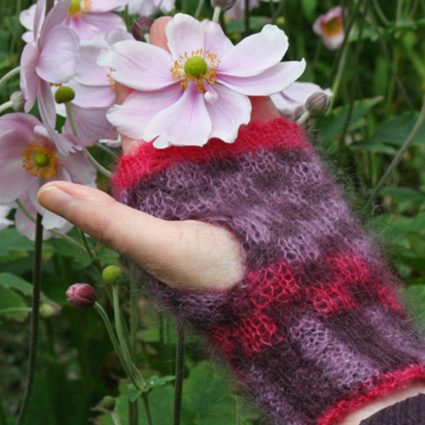 Reversible hand-knitted fingerless mittens with grid pattern in cerise and lilac on purple background knitted using double knit technique