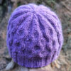 Hand-knitted purple beanie hat with cable pattern inspired by bubbles