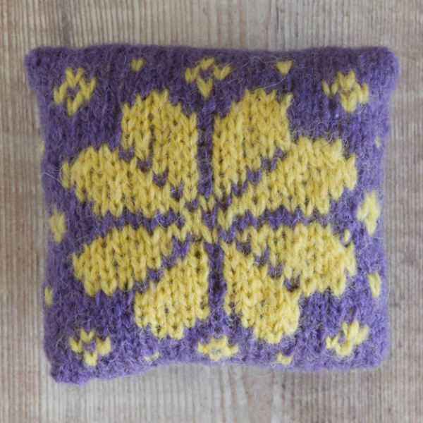 Fair Isle style lavender bag with yellow flower on purple background