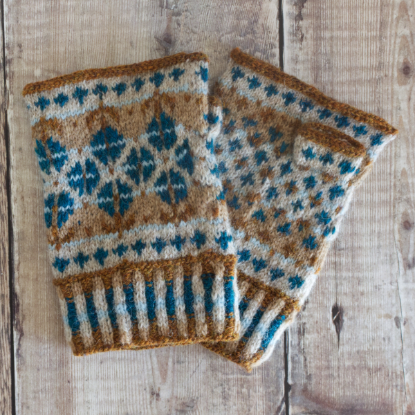 Hand-knitted Fair Isle style fingerless mittens with corrugated rib, simple borders and large pattern featuring blue flowers on beige background