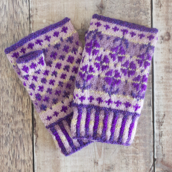 Hand-knitted Fair Isle style fingerless mittens with corrugated rib, simple borders and large pattern featuring violet flowers on lilac and mauve background
