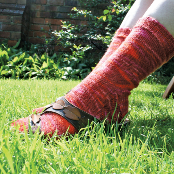 Hand-knitted socks in a red variegated yarn worn by model is sitting in sunny garden