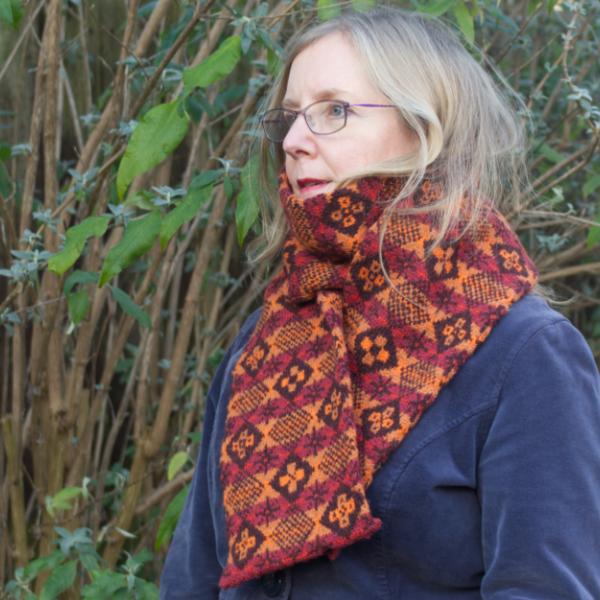 Woman wearing diced pattern Fair Isle scarf with six cross motifs on darker diamonds and one star motif on lighter diamonds