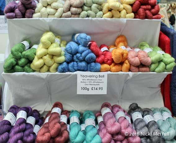 White fabric covered shelves holding hanks of brightly coloured mohair and wool yarn