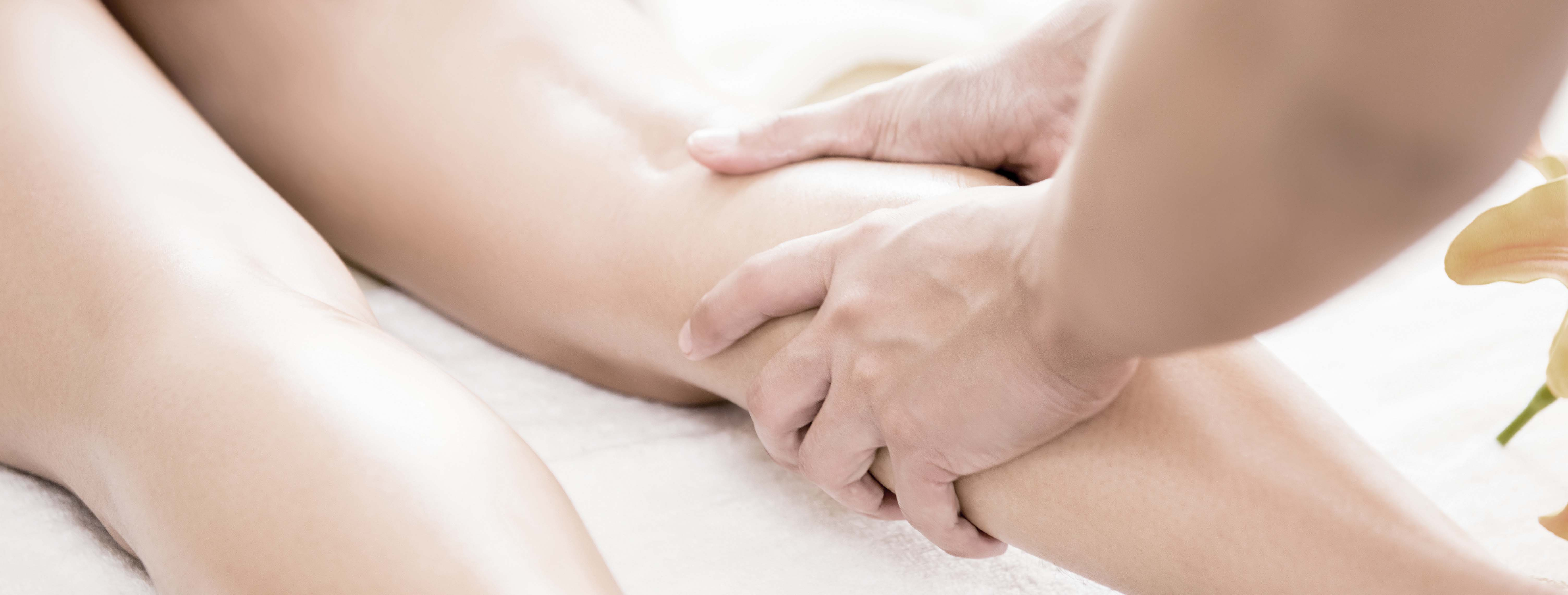 Professional therapist giving relaxing reflexology Thai oil leg massage treatment to a woman in spa - panoramic banner