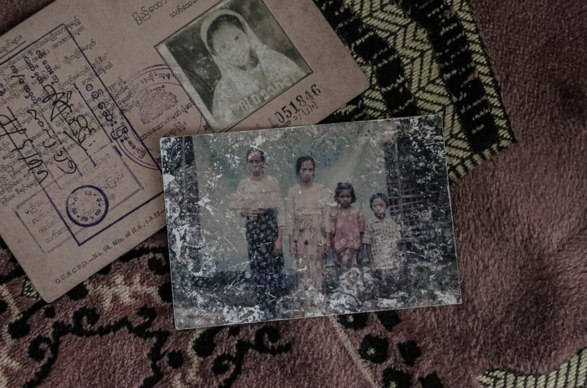 Identity card of Meena* with a family photograph, placed on a prayer rug. While her son was persecuted in the Rakhine State, she managed to escape with her daughter-in-law and grandson in 2017. *Name changed
