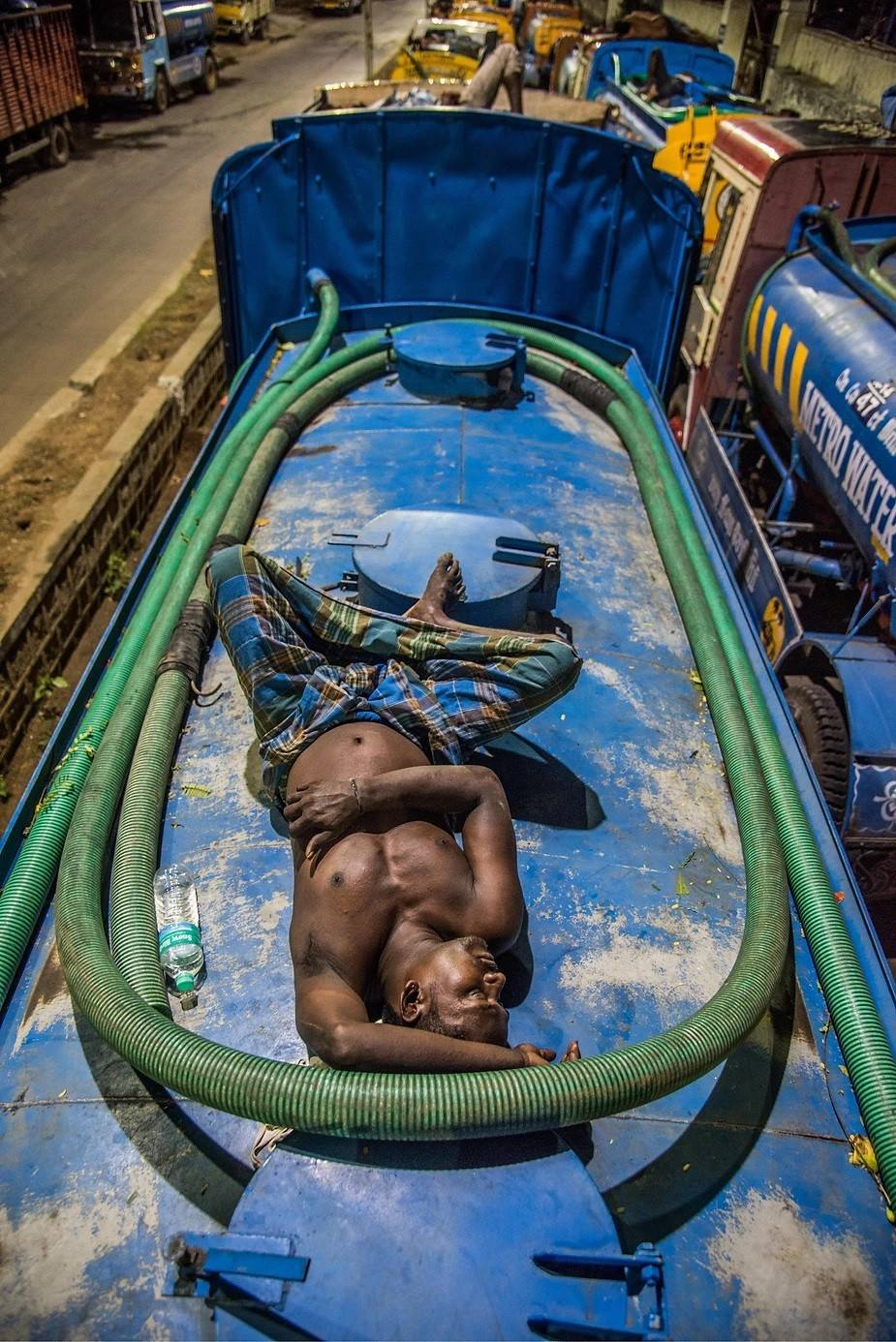 A tired driver sleeping on his water tanker in K.K.Nagar Metro water pumping station, Chennai. Photo by: Steevez Rodriguez/PEP Collective.