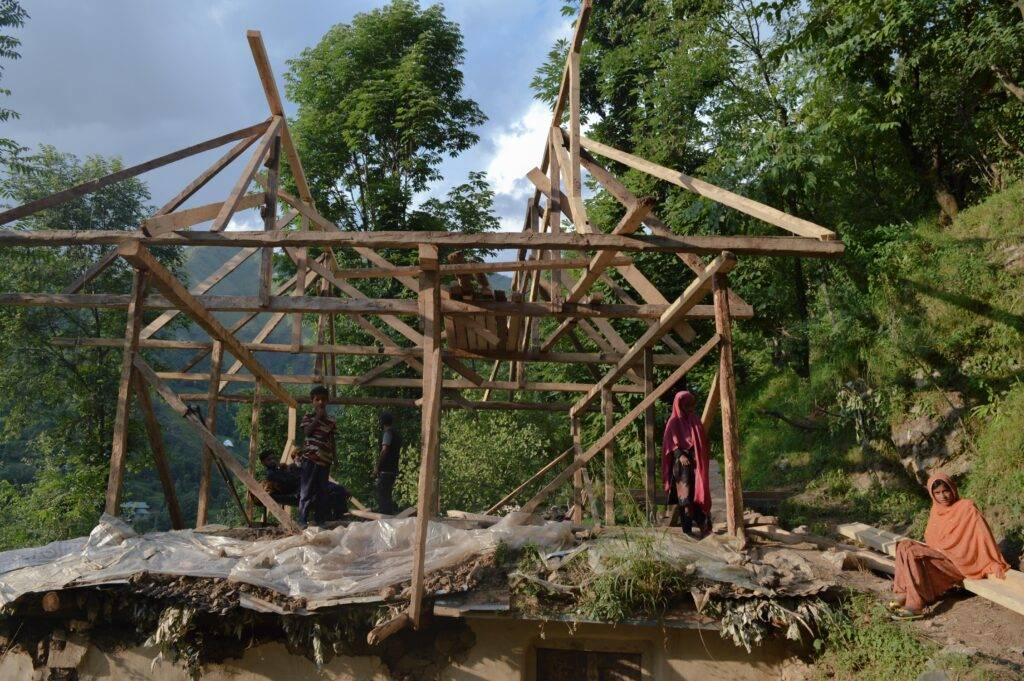 The wooden framework is erected on the roof of a traditional mud house. The line between the kutcha, pukka, and bungalow houses seems to fade in many cases, depending on affordability, site conditions, and space requirements. These hybrid house designs can be quite innovative, but sometimes precarious. Photo by Razia Akhter