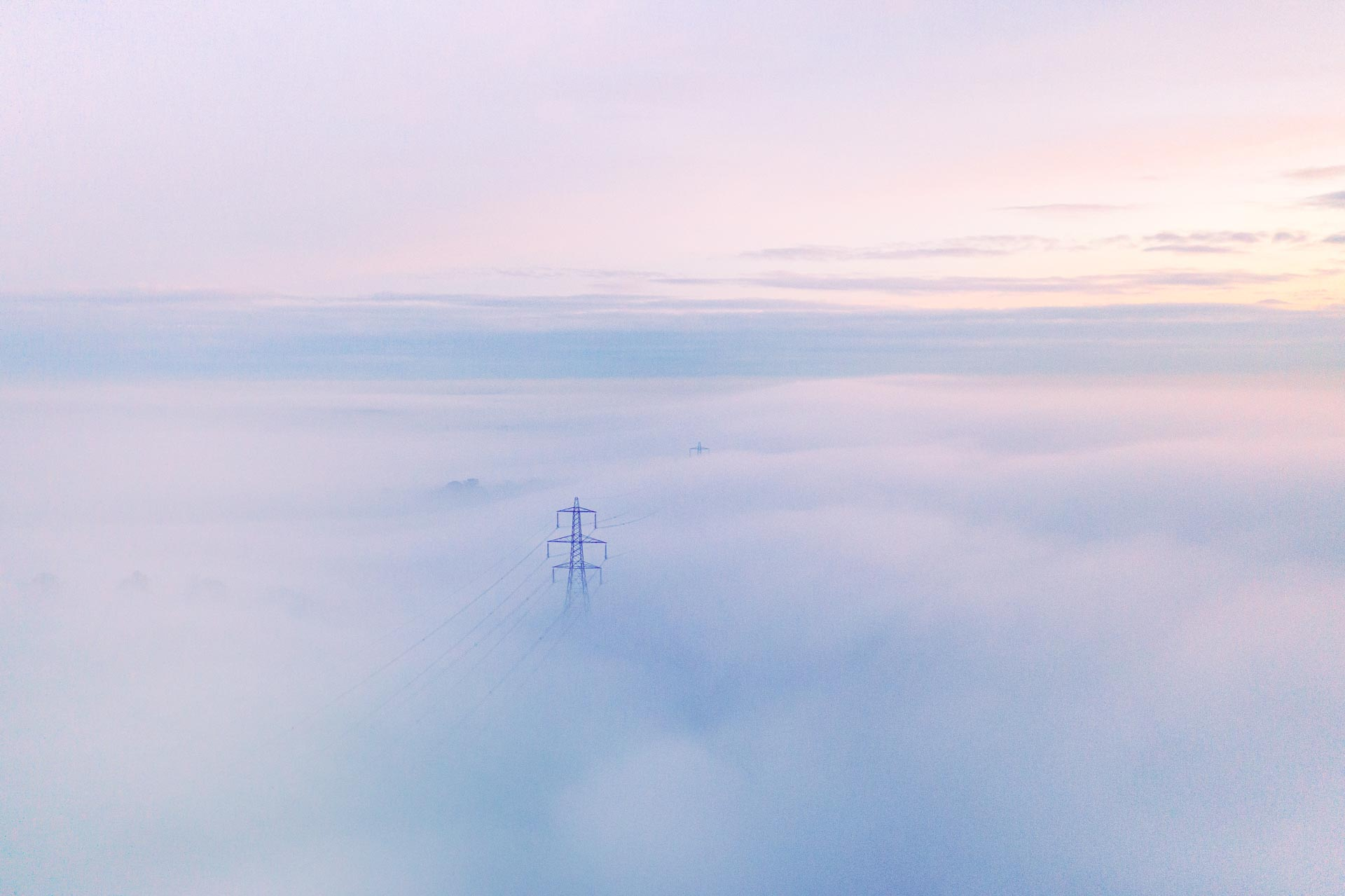 Power lines / pylons cut through the top of the misty landscape, taken from a drone point of view