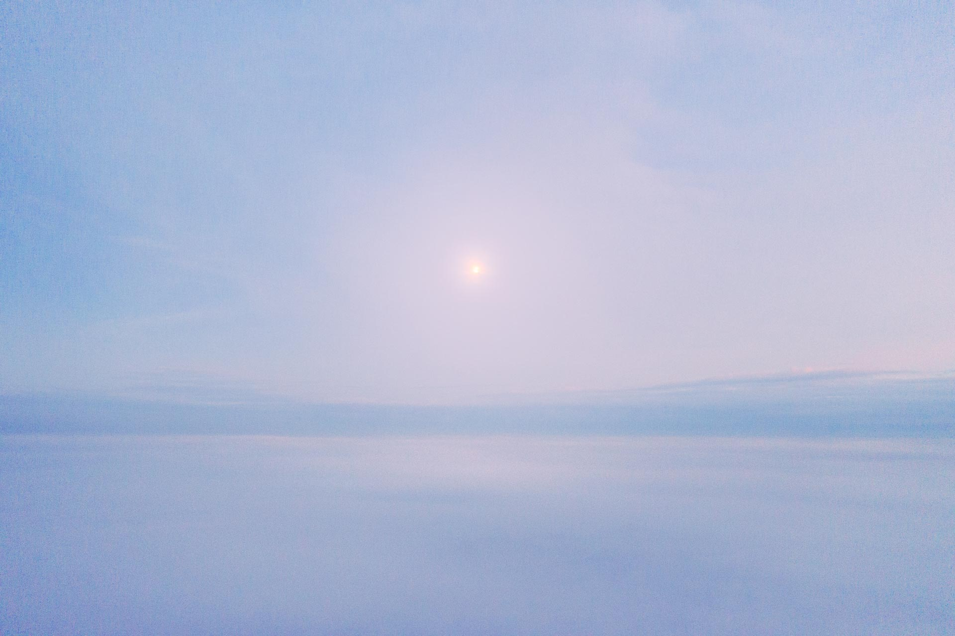 Moonlight illuminates the top of the clouds in a drone landscape